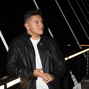 anthony in a black leather jacket and white tee looking off to his left while standing on the bridge between riverfront and minto-brown park salem at night